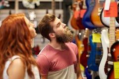 Pares de músicos com a guitarra na loja da música Fotos de Stock
