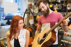 Pares de músicos con la guitarra en la tienda de la música Imagen de archivo