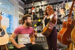Pares de músicos con la guitarra en la tienda de la música Imagenes de archivo