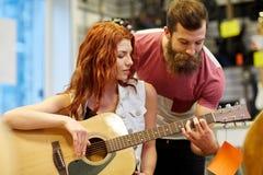Pares de músicos con la guitarra en la tienda de la música Imagen de archivo libre de regalías