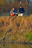 Pares de músicos novos que sentam-se na terra Fotografia de Stock