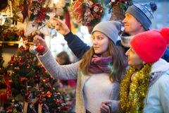 Pares de mediana edad de la familia con la muchacha adolescente que elige deco de la Navidad Fotografía de archivo libre de regalías