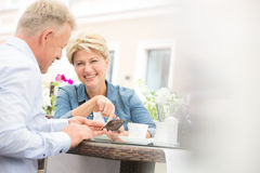 Pares de mediana edad felices usando el teléfono móvil en el café de la acera imagenes de archivo