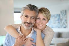 Pares de mediana edad sonrientes en casa Imagen de archivo libre de regalías
