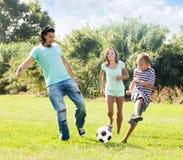 Pares de mediana edad y adolescente que juegan con el balón de fútbol Foto de archivo