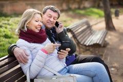 Pares de meia idade que falam no telefone em um banco no parque me imagem de stock