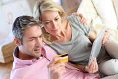 Pares de meia idade que sentam-se no sofá e na e-compra Fotos de Stock Royalty Free