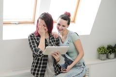Pares de moças bonitas em uma sala com as paredes brancas pela janela Comunique-se e escreva-se no smartphone e foto de stock