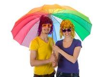 Pares de moda con las gafas de sol y pelucas debajo de un unbrella Imágenes de archivo libres de regalías