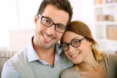 Pares de moda con las lentes que se relajan en sofá Foto de archivo libre de regalías