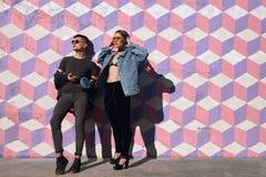 Pares de moda del inconformista que presentan en la calle Foto de archivo libre de regalías
