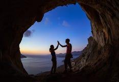 Pares de montanhistas de rocha que dão a elevação cinco e cheering fotografia de stock royalty free