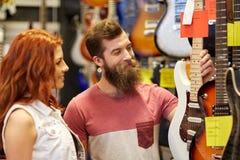Pares de músicos con la guitarra en la tienda de la música Fotos de archivo