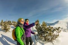 Pares de muchachas turísticas que miran el rastro en las montañas del invierno Imágenes de archivo libres de regalías