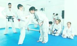 Pares de muchachos que practican nuevos movimientos del karate foto de archivo