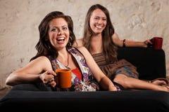 Pares de mujeres de risa con las tazas Imágenes de archivo libres de regalías