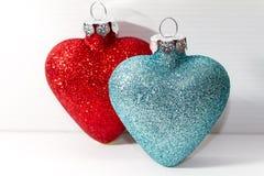 Pares de ornamentos en forma de corazón brillantes de la Navidad Fotografía de archivo libre de regalías