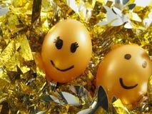 Pares de ovos da páscoa com tiragem do sorriso feliz, no topete dourado Fotos de Stock Royalty Free
