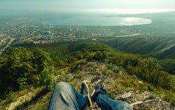 Pares de pés com as sapatas contra o contexto da paisagem pitoresca da cidade e do mar no dia ensolarado Imagens de Stock