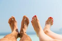 Pares de pés na praia Imagens de Stock