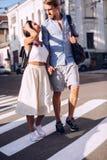 Pares de passeio que falam na faixa de travessia na cidade Fotografia de Stock