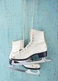 Pares de patines de hielo en fondo de madera azul Fotos de archivo
