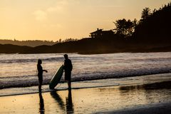 Pares de personas que practica surf en la playa de Tofino en la puesta del sol Imágenes de archivo libres de regalías