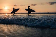 Pares de personas que practica surf sobre puesta del sol en la costa costa Foto de archivo