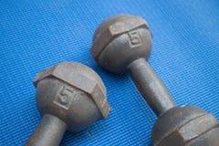 Pares de pesa de gimnasia del hierro 5 kilogramos en la estera azul de la yoga Imágenes de archivo libres de regalías