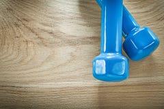 Pares de pesas de gimnasia azules en concepto de la aptitud del tablero de madera Imágenes de archivo libres de regalías