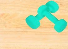 Pares de pesas de gimnasia azules en fondo de madera Foto de archivo libre de regalías