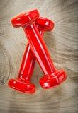 Pares de pesas de gimnasia rojas en el concepto de madera de la aptitud de la opinión superior del tablero Foto de archivo libre de regalías