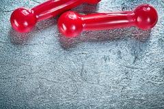 Pares de pesas de gimnasia rojas en el concepto de plata de la aptitud del fondo Foto de archivo