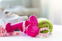 Pares de pesas de gimnasia rosadas de la aptitud con la cinta del centímetro en brillante Fotos de archivo libres de regalías