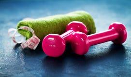 Pares de pesas de gimnasia rosadas de la aptitud con la cinta del centímetro en vagos oscuros Imagenes de archivo