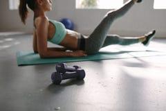 Pares de pesas de gimnasia con la mujer que estira en el gimnasio Foto de archivo
