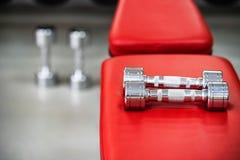 Pares de pesas de gimnasia de plata en gimnasio Fotografía de archivo libre de regalías