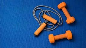 Pares de pesos alaranjados e corda de salto no fundo azul da esteira da ioga Imagens de Stock