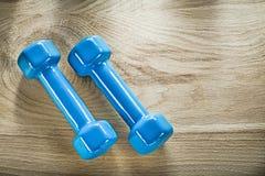 Pares de pesos azuis do peso no conceito da aptidão da placa de madeira Fotos de Stock