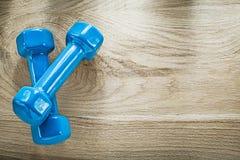 Pares de pesos azuis do peso no spor horizontal da opinião da placa de madeira Fotografia de Stock Royalty Free