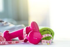 Pares de pesos cor-de-rosa da aptidão com a fita do centímetro em brilhante Imagens de Stock