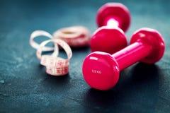 Pares de pesos cor-de-rosa da aptidão com a fita do centímetro em vagabundos escuros Fotografia de Stock