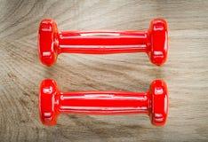 Pares de pesos vermelhos do peso no conceito da aptidão da placa de madeira Fotos de Stock Royalty Free