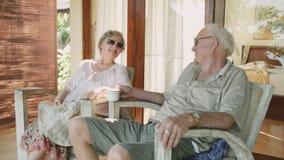 Pares de pessoas adultas nos óculos de sol que sentam-se no jardim da frente de sua casa video estoque