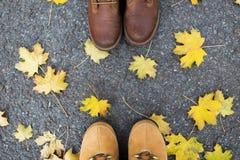 Pares de pies en botas y hojas de otoño Fotografía de archivo libre de regalías