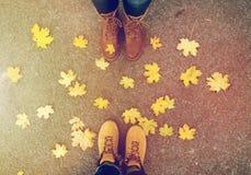 Pares de pies en botas y hojas de otoño Imagen de archivo