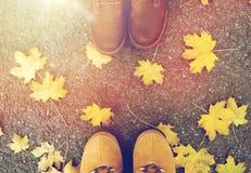 Pares de pies en botas y hojas de otoño Fotos de archivo