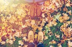 Pares de pies en botas y hojas de otoño Fotografía de archivo