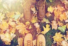 Pares de pies en botas y hojas de otoño Imágenes de archivo libres de regalías