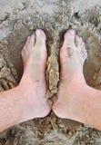Pares de pies en la arena Imágenes de archivo libres de regalías